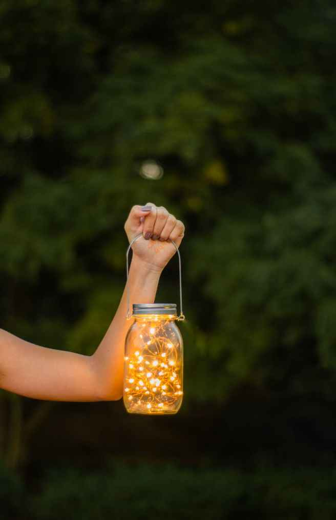 photo of woman s hand holding a mason jar with string lights