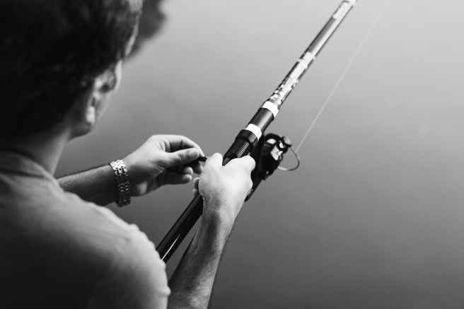 grayscale photography of man holding fishing rod